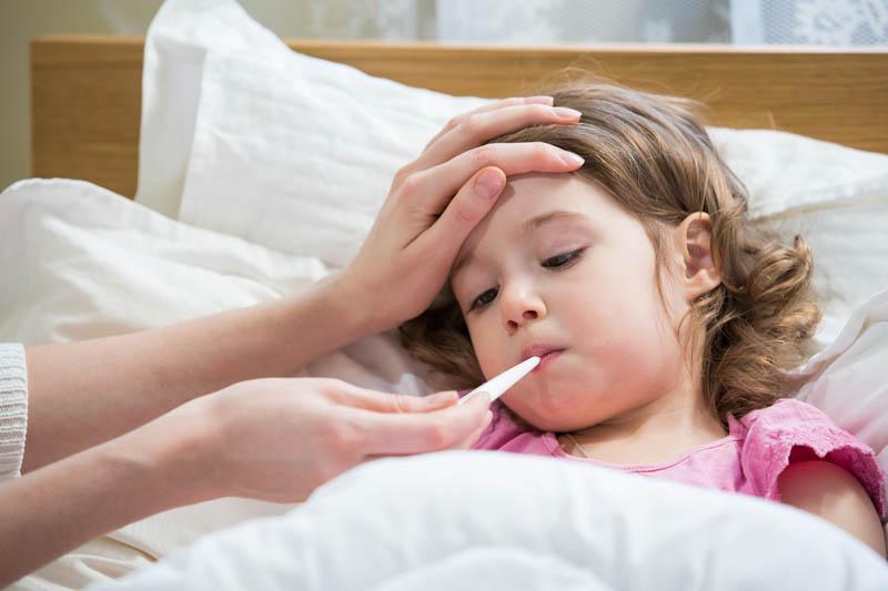 niña con gripe mamá tomando la temperatura